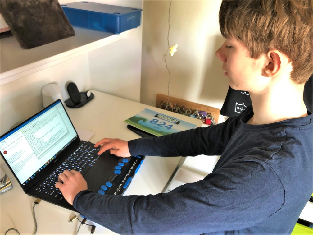 Side view of Theo using his Braille display laptop